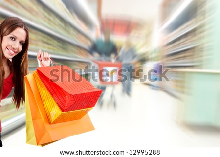 Shopping woman holding bag over blurred supermarket background. - stock photo