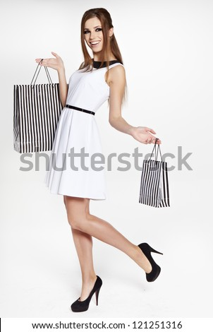 ... woman holding bags, isolated on gray studio background. - stock photo