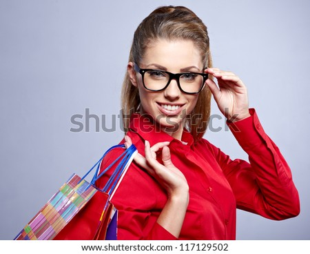 Shopping woman holding bags, isolated on grey studio background. - stock photo
