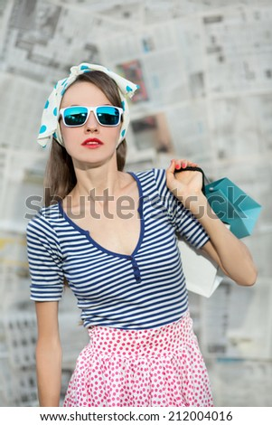 Shopping woman holding bags on grey newspaper background. Summer shopping woman wearing sunglasses - stock photo
