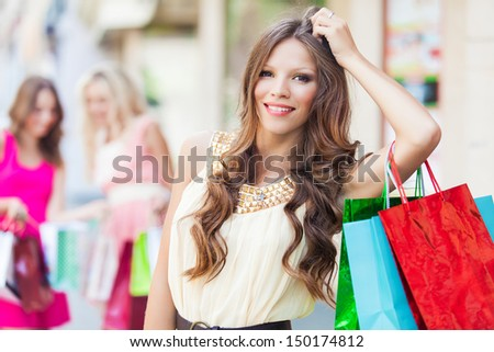 Shopping woman holding bags with a group of friends at the background