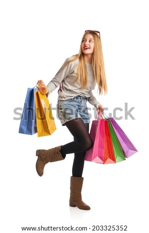 Shopping woman holding shopping bags looking up to the side on white background at copy space - stock photo