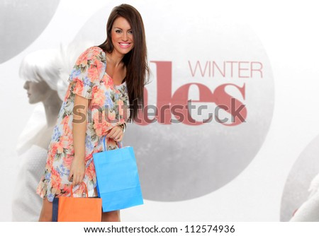 Shopping woman in front of winter sales window - stock photo
