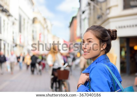 Shopping woman lifestyle in Copenhagen street. Scandinavian travel, tourist adult alone walking looking at shops during fall or spring in famous European city center in Denmark. - stock photo