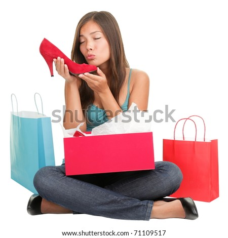 Shopping woman loves shoes. Funny cute image of young woman kissing high heels shoes after shopping. Asian Caucasian woman sitting isolated on white background. - stock photo