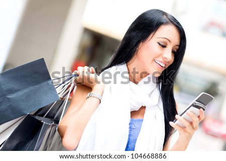 Shopping woman sending a text message on her cell phone - stock photo