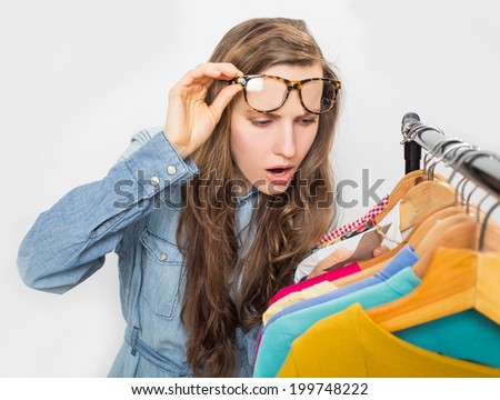 Shopping woman shocked over price tag. Funny shopper woman staring amazed at price over light grey background - stock photo