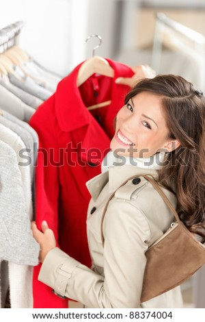 Shopping. Woman shopper looking at jacket / coat in clothes store. Beautiful smiling young woman - mixed race Asian / Caucasian - stock photo