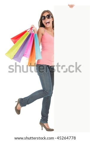 Shopping woman showing commercial sign. Full length picture of a beautiful young mixed race woman holding a blank billboard sign while standing with many shopping bags. Isolated on white background. - stock photo