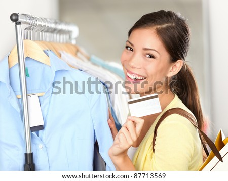 Shopping woman showing credit card or gift card by clothes rack. Happy smiling mixed race Caucasian / Asian female shopping in store. - stock photo