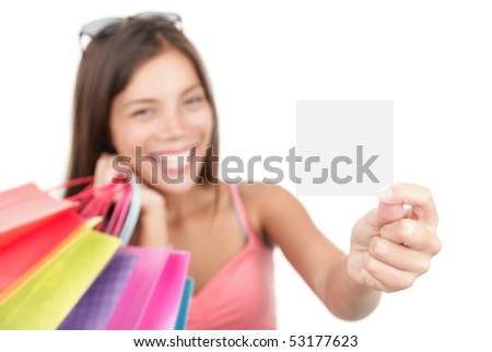Shopping woman showing sign or blank card. Chinese Asian / Caucasian isolated on seamless white background. Focus on the blank sign / card.