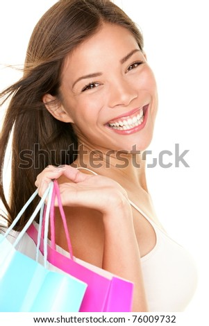 Shopping woman smiling holding shopping bags. Closeup portrait of beautiful young mixed race Asian Caucasian woman with gorgeous smile isolated on white background. - stock photo