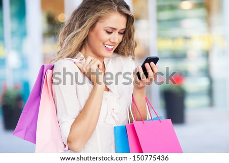 Shopping woman text messaging - stock photo