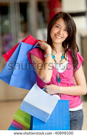 Shopping woman with bags smiling at the mall - stock photo