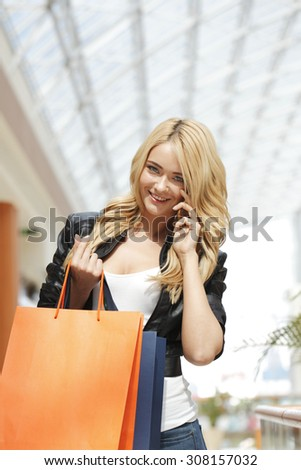 Shopping woman with bags talking on the phone in mall