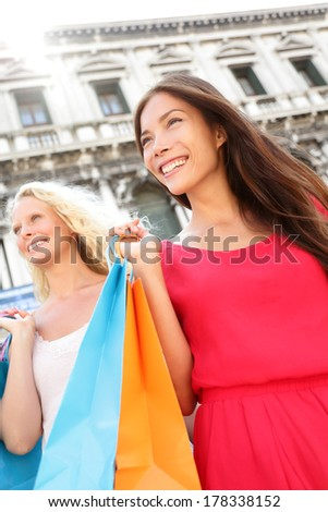 Shopping women city portrait beautiful fashion woman smiling happy in Venice, Italy. Two girlfriends holding shopping bags outside. Beautiful Asian and Caucasian woman, Piazza San Marco Square.