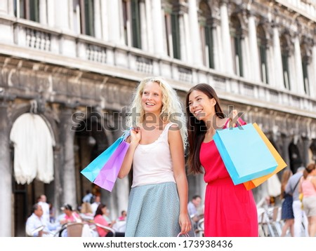 Shopping women - girl shoppers holding shopping bags in Venice. Portrait of beautiful girlfriends smiling happy together having fun on San Marco Square, Venice, Italy. Caucasian and Asian models. - stock photo