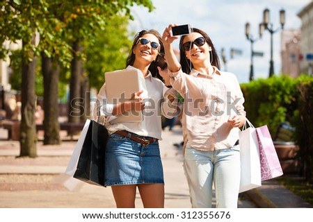 Shopping women happy holding shopping bags, laptop walking having fun laughing in street. Beautiful young caucasian  girlfriends make selfie n the street and smilling. - stock photo