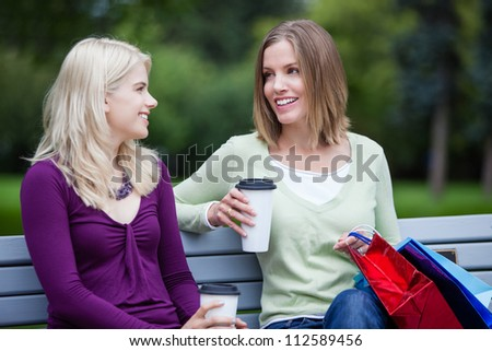 Shopping Women with Takeaway Coffee on bench. - stock photo