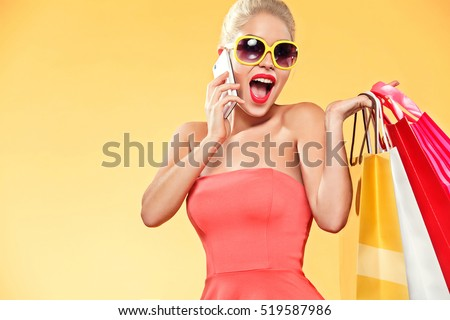 Shopping. Young smiling woman holding bag and mobile phone make her thumb up in black friday holiday. Girl on yellow background with copy space