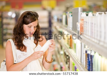 Shopping - young woman holding bottle of shampoo in supermarket - stock photo