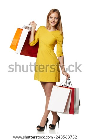 Shopping young woman in the yellow with bags isolated on white background - stock photo