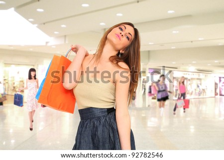 Shopping young woman smiling with bags  in the shopping mall.
