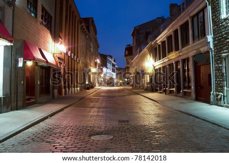 Shops and illuminated street of Old Montreal at dusk - stock photo