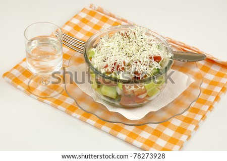 Shopska mixed salad in glass plate,ouzo and napkin on white - stock photo