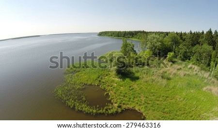 Shore of water reservoir with forest under blue sky at sunny summer day. Aerial view. - stock photo