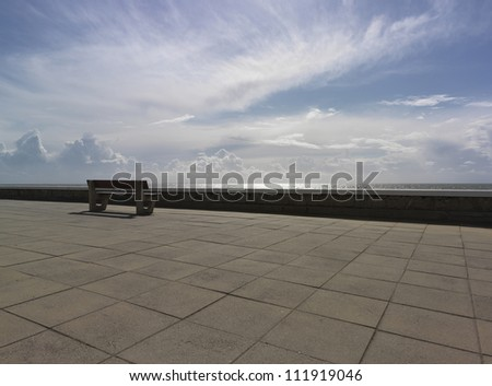 shore promenade with bench and the sea in background - stock photo