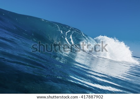 Shorebreak surfing tube wave. Pipeline in daylight with light of sun. Green Blue Ocean Water. Surfing template design with nobody. White splashes and ocean foam. Sky with no clouds. Surfing Rip Curl.