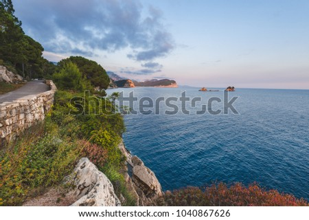 Shoreline and Adriatic sea Montenegro landscape on the path to Petrovac. Rocks, water and Sveta Nedjelja island by sunset near Perazica Do and Petrovac. Wild Adriatic coast panoramic scene.