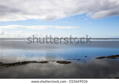 shoreline of Ameland Island, with view over the wadden sea, with tourmented sky and clouds reflecting in water at dawn - stock photo