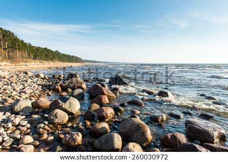 Shoreline of Baltic sea beach with rocks and sand dunes under clouds