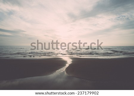 Shoreline of Baltic sea beach with rocks and sand dunes under clouds - retro, vintage style look - stock photo