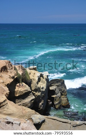 Shoreline rocks jut out into the water in La Jolla, California. - stock photo