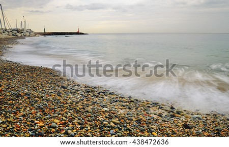 shoreline with soft water andcloudy sky in autumn - stock photo