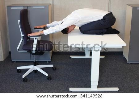 short break for yoga in the office - caucasian male professional exercising - stock photo
