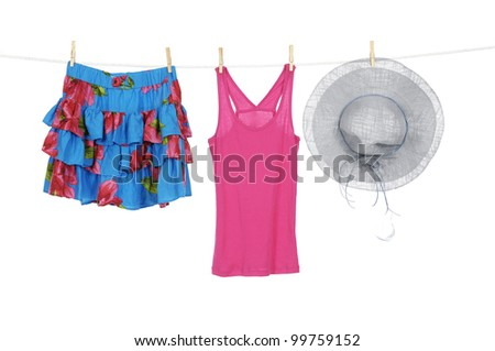 Short flower skirt and red sundress and hat on a clothespins on rope