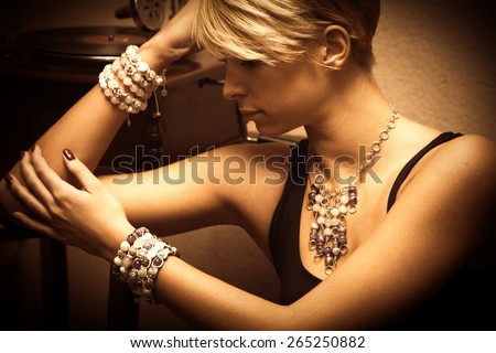 short hair blond elegant young woman portrait wearing jewelry, necklace and lot of bracelets, indoor shot, side view - stock photo