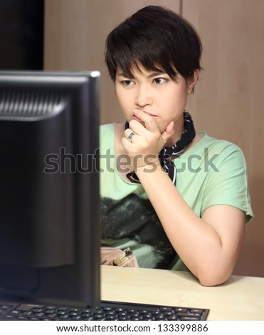 Short Hair Girl Looking Computer with Serious Face - stock photo