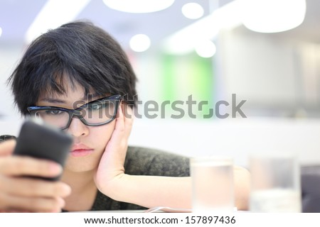 Short Hair Girl Looking Mobile Phone and Feeling Unhappy - stock photo