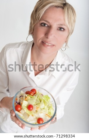 Short haired blond woman holding a salad bowl - stock photo