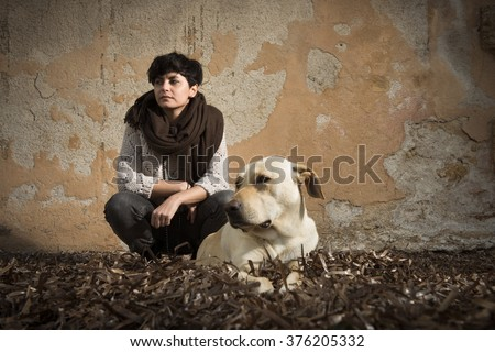 short haired brunette girl is sitting with a white dog wearing a jumper and a pair of jeans - stock photo