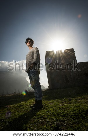 short haired brunette girl is standing on the lawn wearing a jumper, a pair of jeans and boots with the sun shining ins the background - stock photo