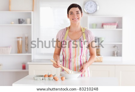 Short-haired brunette woman preparing a cake in a kitchen