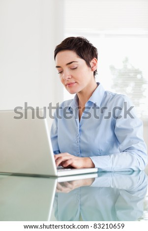 Short-haired businesswoman with a laptop in an office - stock photo