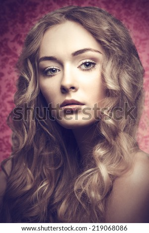 Short portrait of blonde beautiful young girl with long curly hair on pink backgroung is looking in camera