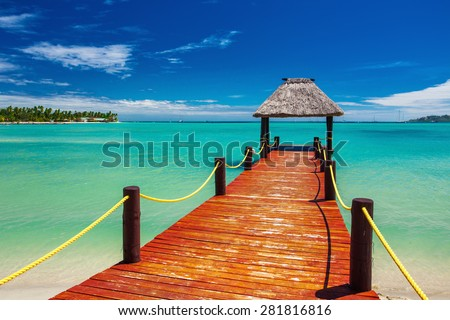 Short red wooden jetty extending to tropical ocean on Fiji Island - stock photo